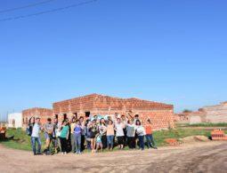 Familias seleccionadas para el proyecto 'Bienvenidos a mi pueblo' frente a las casas en construcción. FUNDACIÓN ES VICIS